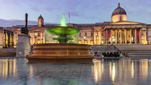 London National Gallery and Trafalgar Square and one of its fountains at dusk.
