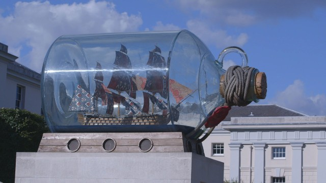 A ship in a bottle exhibit against the blue skies at the National Maritime Museum.