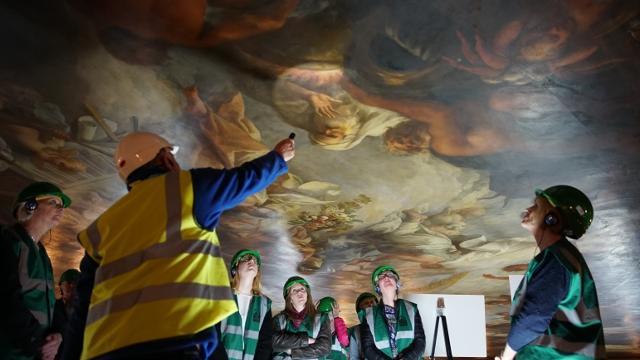 Restorers studying a fresco