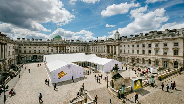 The courtyard at Somerset House, with a marquee in the centre and people milling around the courtyard.