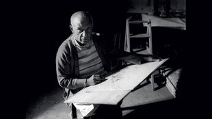 A black-and-white photograph of Pablo Picasso sitting down, looking towards the camera as he draws on a canvas in front of him.