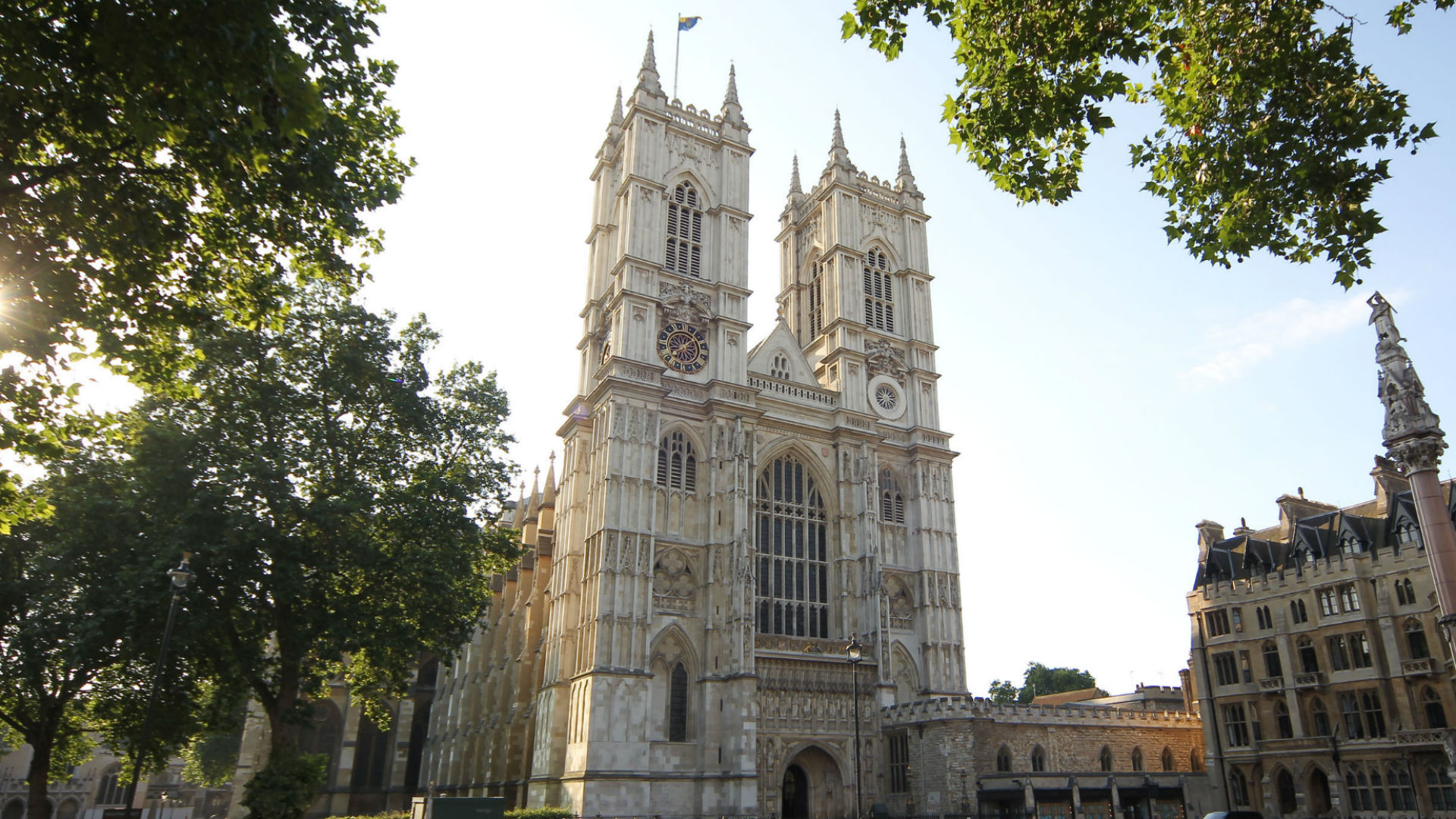 Exterior view of Westminster Abbey with leafy trees and sunshine