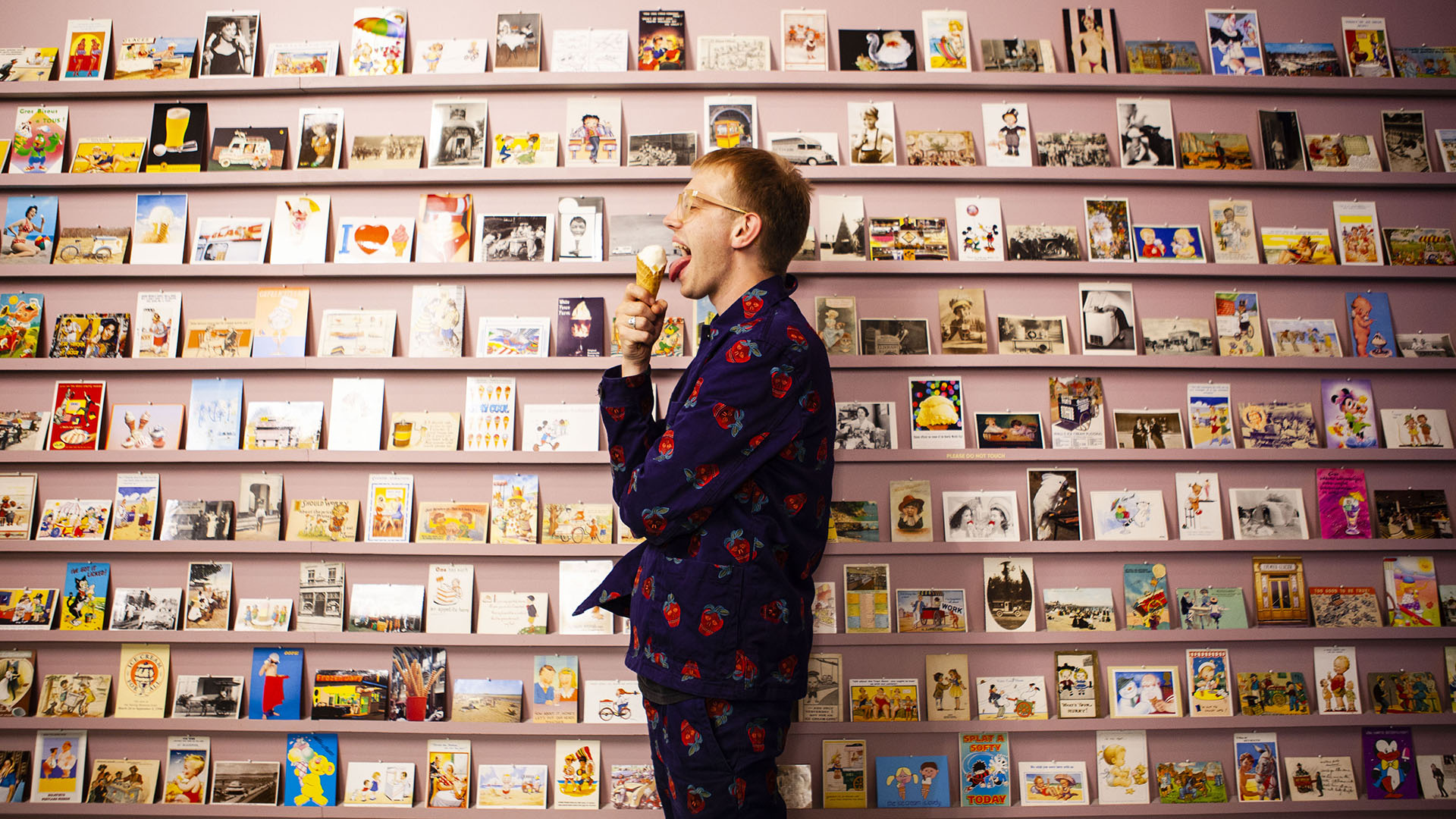 A man licks and ice cream cone in front of a pink wall lined with rows of ice cream themed postcards.