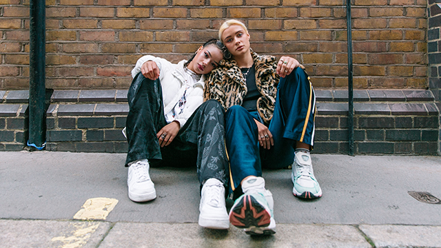 Two women wearing trainers, sitting on the pavement against a brick wall.