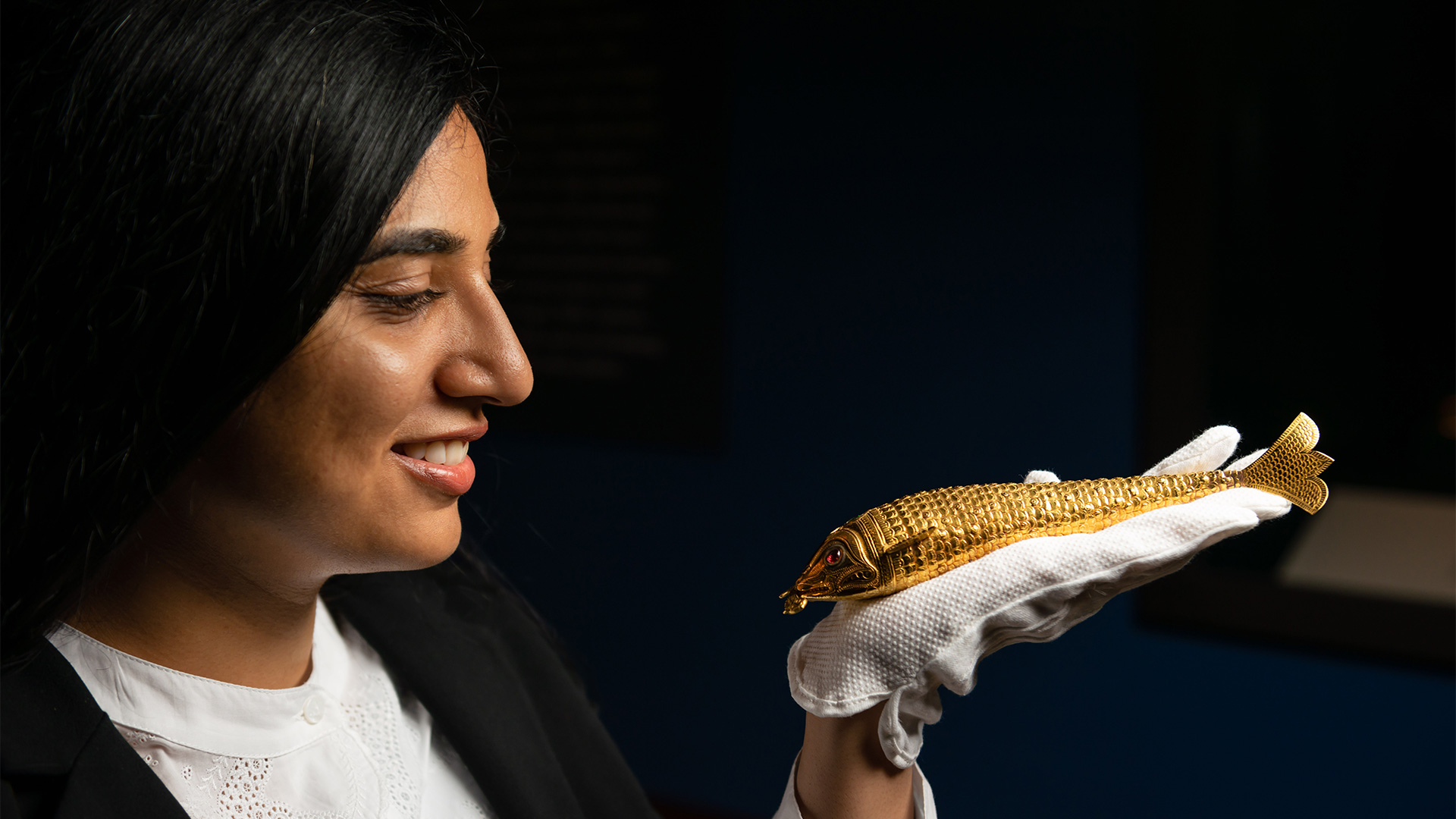 A Royal Collection Trust member of staff holds a gold ornamental fish.
