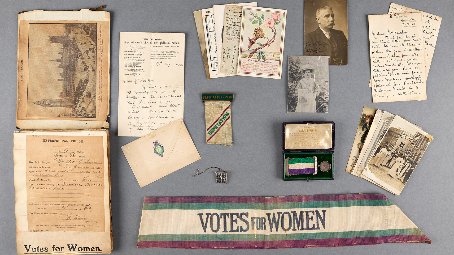 Notebooks, letters, photographs and a sash reading 'Votes for Women'.