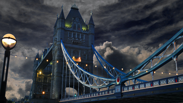Tower Bridge in a dark setting with dark clouds and the bright blue railings.