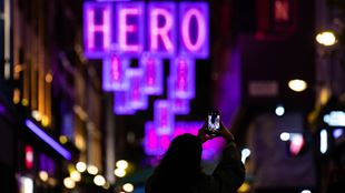 A person taking a picture of purple-lit Carnaby Christmas lights.