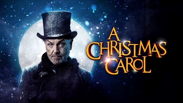 A poster of a character from A Christmas Carol – The Musical Staged Concert with a hat on.