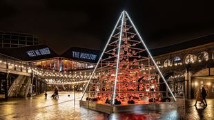 The Terrarium Tree in Coal Drops Yard, made up of hanging terrariums and baubles, light up in red.