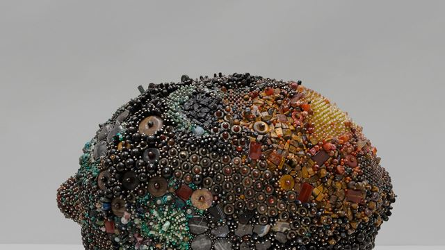 A photo of a lemon-shaped sculpture covered in jewels of different colours.