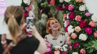 A lady taking a picture inbetween the flower displays at the RHS Chelsea Flower Show.