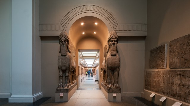 A corridor at the British Museums, with two sculptures gating it.