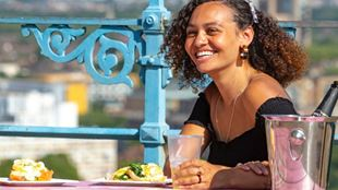 A woman smiling while sitting at a dining table outside.