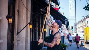 A man opening up the blinds of a shop with a wooden stick.