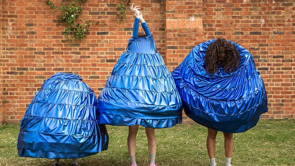 Three people line up, one crouched, one stretching up and one bent over, all wearing conical-shaped blue costumes.