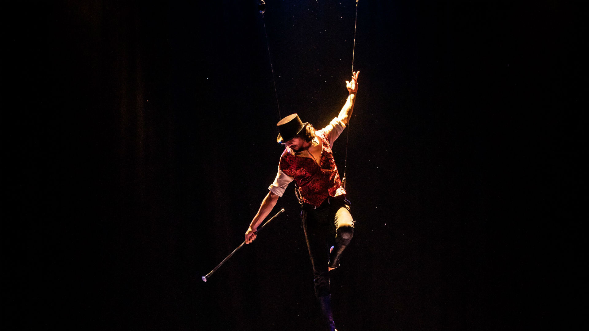 A man hanging on a trapeze during a circus performance at the Greenwich Circus Festival.