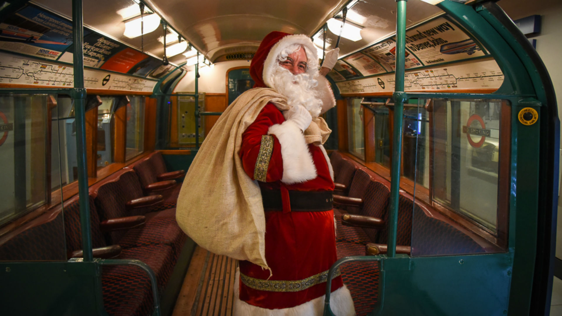 A man dressed in a Santa outfit holding a sack, in a London Tube.