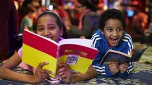 Two children smiling as they read books during the Imagine Children's Festival in Southbank.