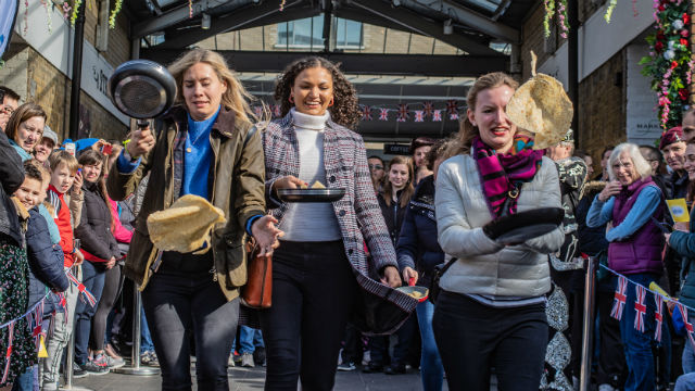 Three people flipping pancakes as they run at the annual Pancake Day race at Greenwich Market.