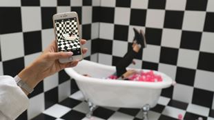 A person taking a picture of someone laying upside down in a bathtub full of pink balls.
