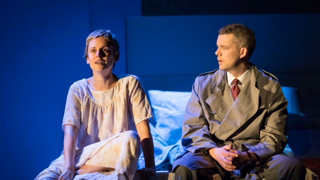 Two actors sitting on a bed with theatre spotlights beaming on them. One is looking into the distance.