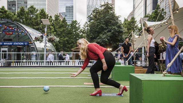 A blonde woman in red top and shoes throwing a ball down the green lawn during Festibowl in Canary Wharf.