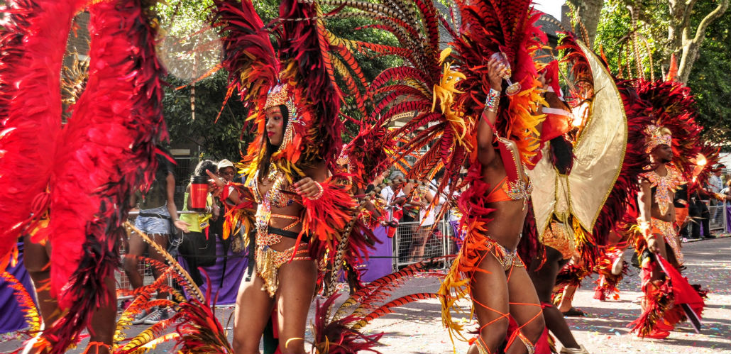 Two women dressed in red traditional carnival costumes dancing at during the Notting Hill Carnival parade.