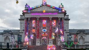 Several neon lights hanging on the Tate Britain building.