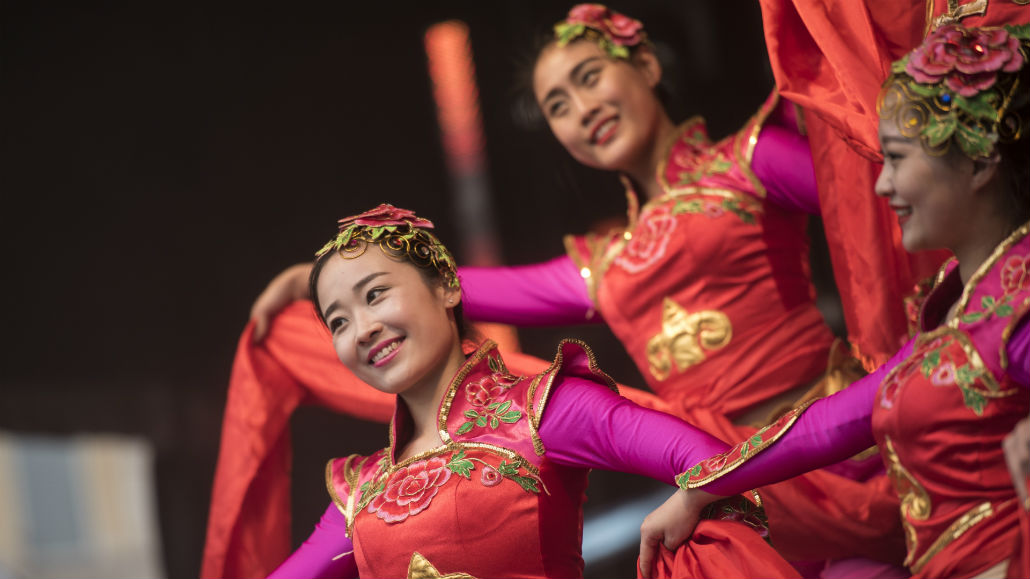 Three ladies in red outfits dancing during the annual Chinese New Year celebrations at Trafalgar Square.