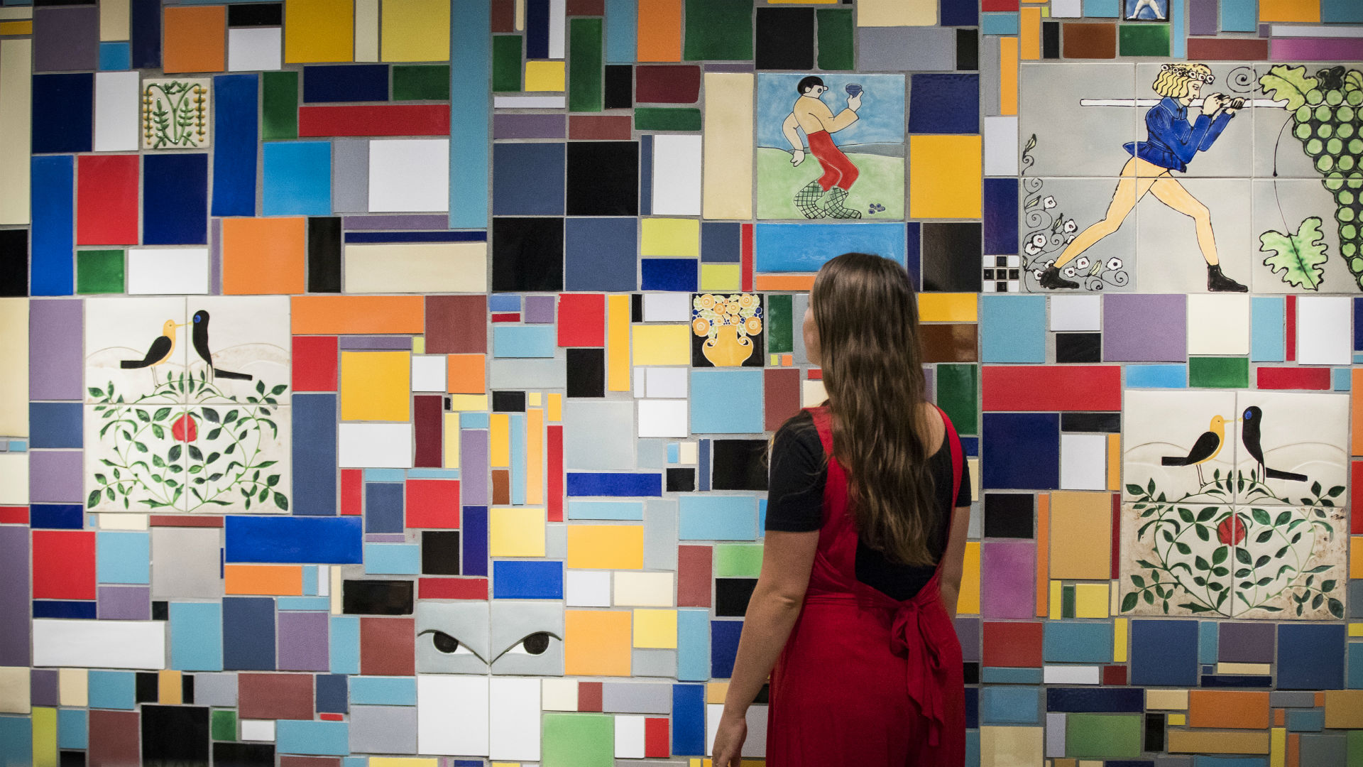 A girl looking at the colourful artworks during the Into The Night: Cabarets And Clubs In Modern Art exhibition.