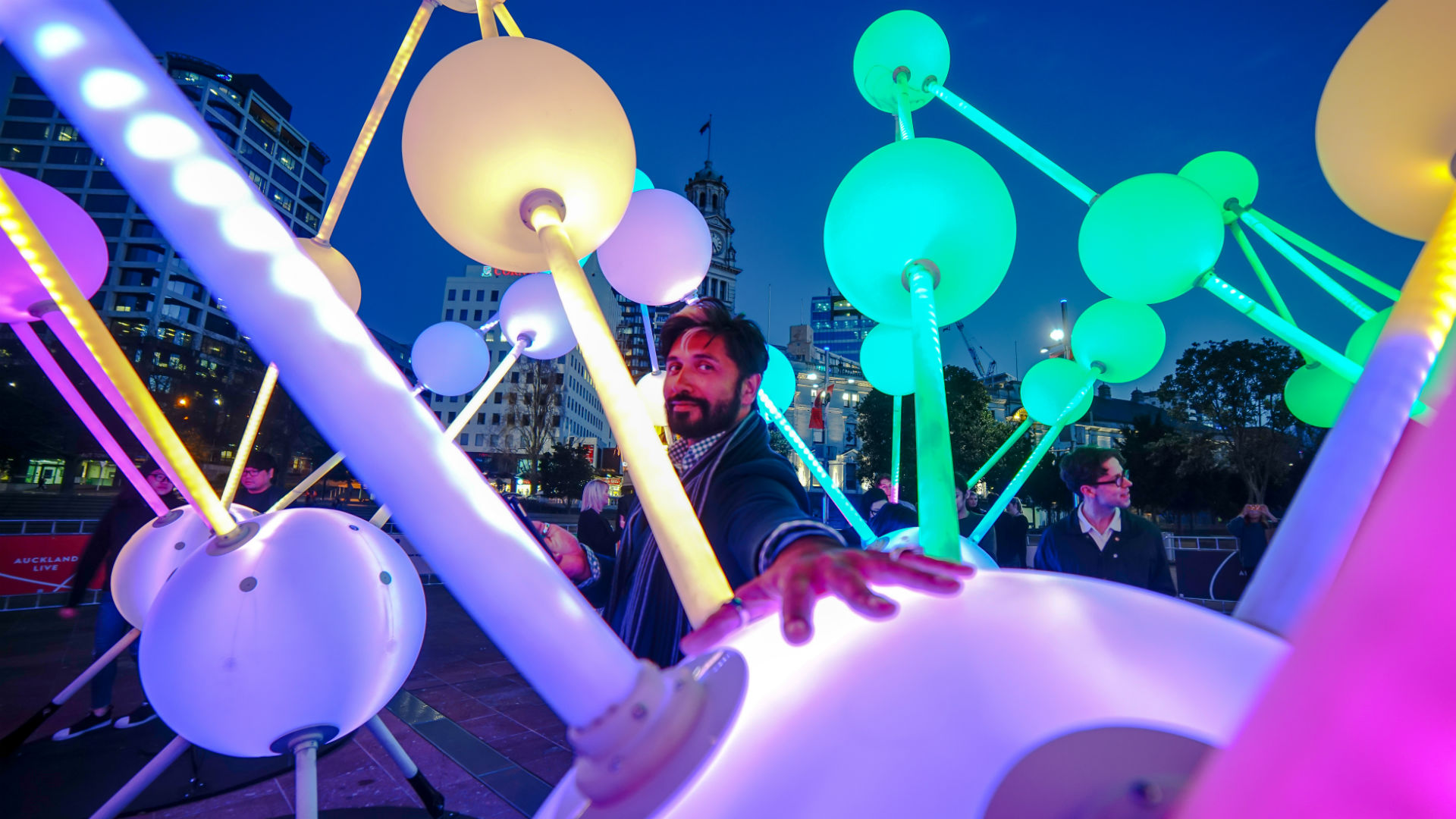 A man standing among colourfully lit orbs during the Winter Lights Festival at Canary Wharf.