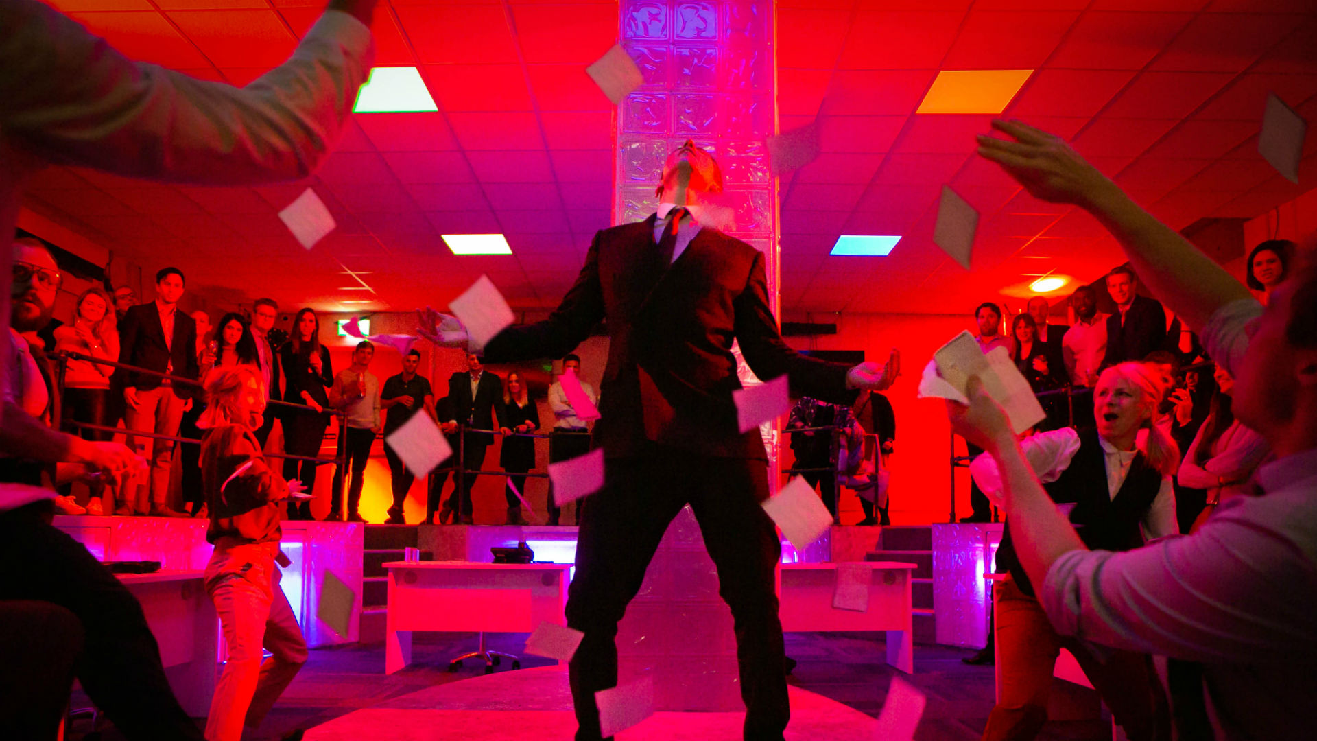 A man standing on stage with money-like paper flowing around, while people surround him watching, in a red-lit room.