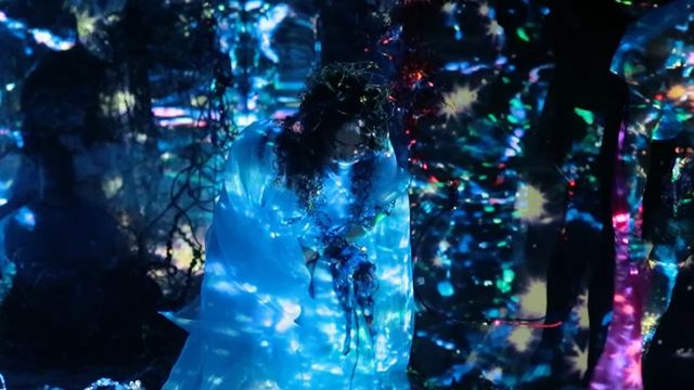 A woman standing in the dark with colourful lights illuminating the space.