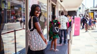A woman social distancing, standing in line to a shop.