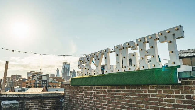 A big sign of the Skylight Rooftop Bar on a sunny day with London panorama in the background.