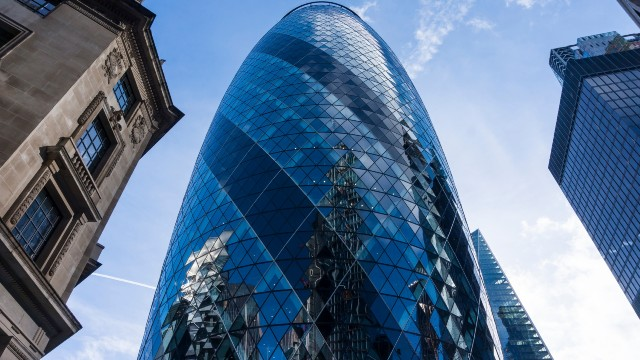Gherkin building from a low perspective with blue skies in the background.