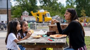 A lady and two children sitting at a picnic table, eating food and laughing at the Royal Air Force Museum.