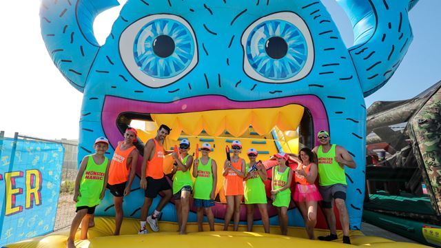 People in flourescent vests standing on an inflatable course with a blue blow-up monster in the background.