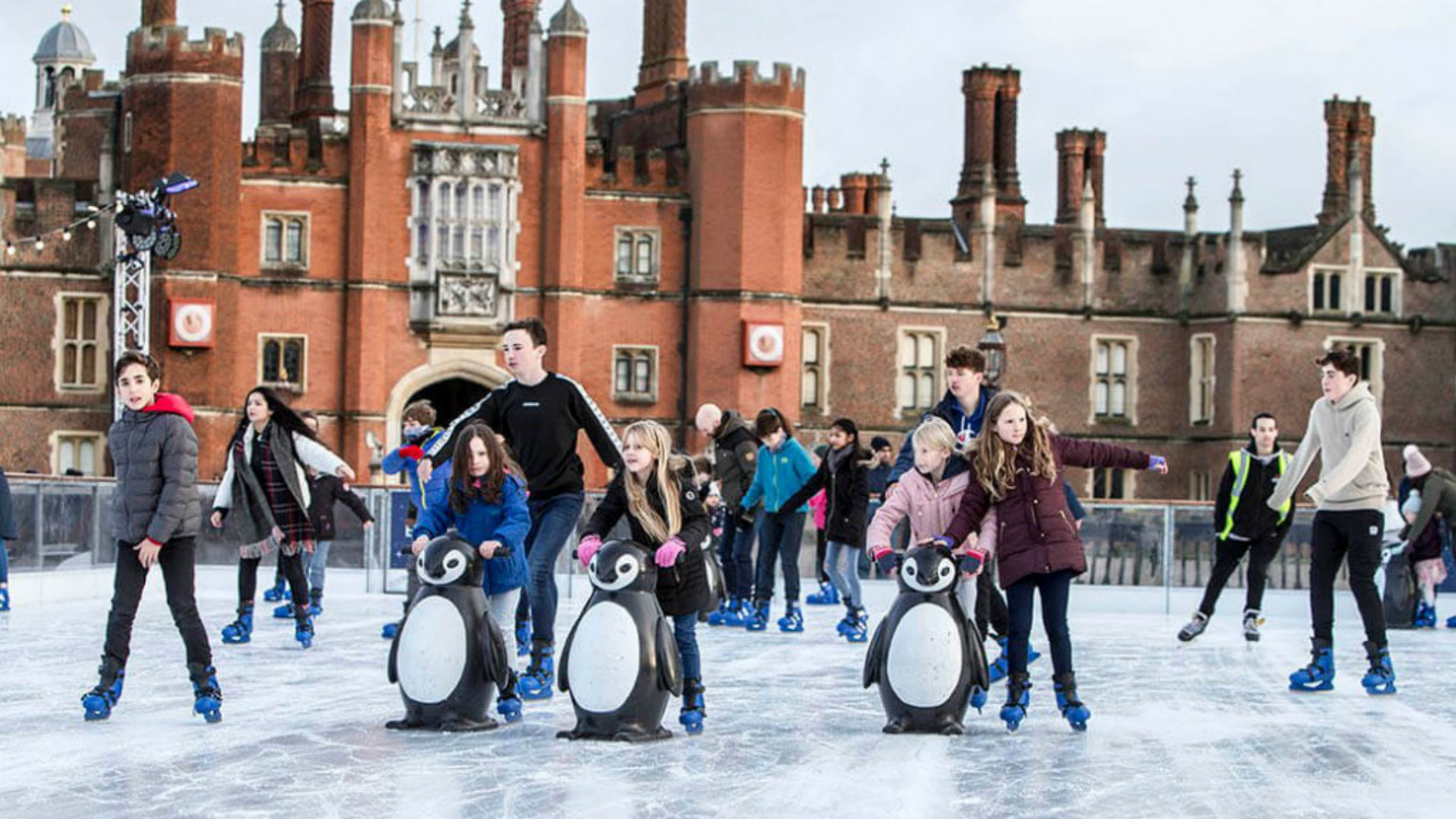 A photo of families skating at the Hampton Court Palace Ice Rink, with the palace in the background.