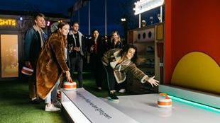 A photo of people enjoying the Google Curling at The Winter Carnival at John Lewis Rooftop.