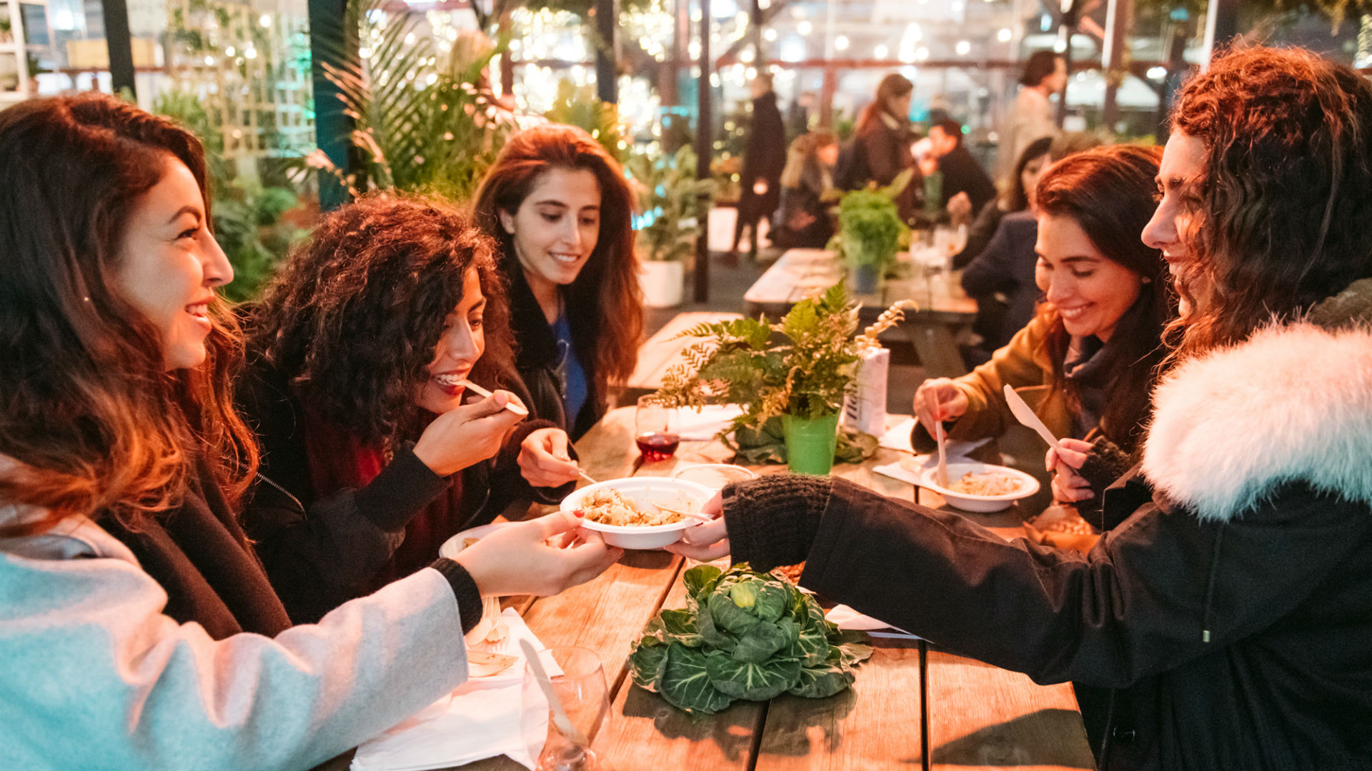 A photo of people sharing their food at the Taste of London.