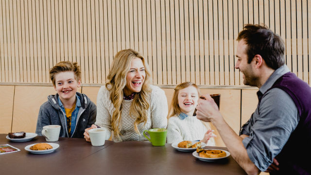A family of four laughing over breakfast.