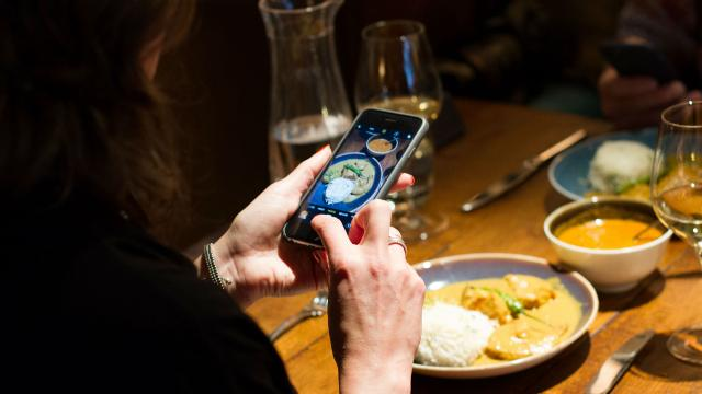 A photo of a person taking a picture of the food using a phone.