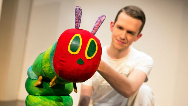 An actor holding the The Very Hungry Caterpillar puppet.