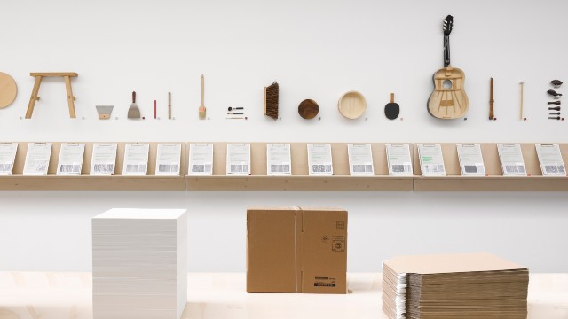 An exhibition in a bright room including wooden musical instruments and boxes.