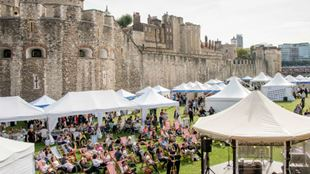 A photo of the grounds of Tower of London covered with tents and a crowd.