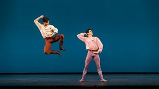 One man standing and one man jumping during a ballet performance of Dance at a Gathering.