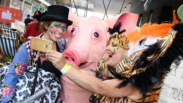 Visitors taking a picture with a pig during the Smithfield Street Party: A Beastly Adventure.
