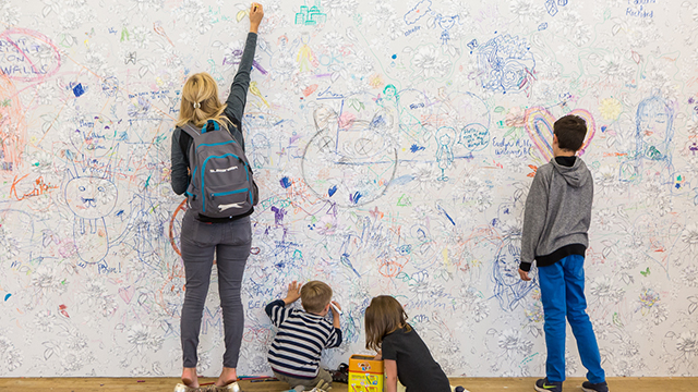 A lady and three children draw on a white wall, which already has a lot of drawings on it.
